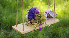 A bouquet of flowers rests on a wooden swing Stock Footage