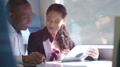 4k Happy attractive ethnic couple using computer tablet on train journey. - stock footage