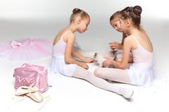 Three little ballet girls sitting and posing together - stock photo