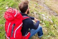 Man hiker with red backpack sitting on ground Stock Photos