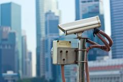 CCTV surveillance camera in Singapore with skyscapers in background Kuvituskuvat