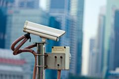 CCTV surveillance camera in Singapore with skyscapers in background - stock photo
