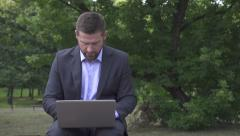 Businessman sitting in park and working on laptop. Stock Footage