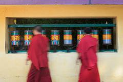 Buddhist monks passing and rotating prayer wheels on kora around Tsuglagkhang Stock Photos