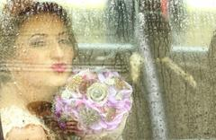 Stock Photo of Bride having fun in the car on a rainy day