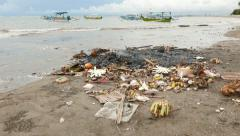 Burning debris and Canang sari remains on Balinese beach, close view Stock Footage