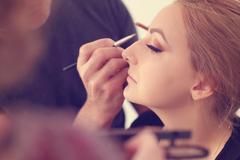 Beautiful bride getting professional makeup done Stock Photos