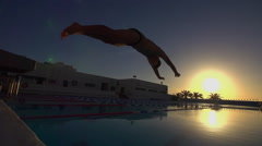 Swimmer Dives into Pool at sunset. Stock Footage