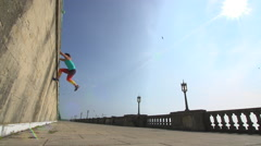 Female Le Parkour Exponant runs at wall and climbs over it! Stock Footage