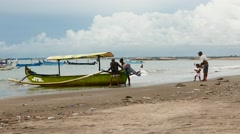 Two men push outrigger canoe from beach shoal to water Stock Footage
