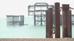 Women Running On Beach With Broken Down Pier in Sea. Stock Footage