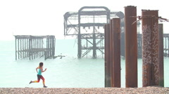 Women Running on Beach With Pier Remnants in Sea. Stock Footage