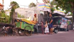 Fry corn cooking wheel cart on busy street, small girls with father waiting Stock Footage
