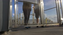 Couple leaves large steel gate doors Stock Footage