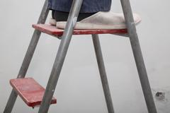 House Renovation. Master in the uniform on the ladder - stock photo