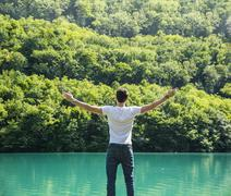 Young man, arms spread open enjoying freedom in front of lake Stock Photos
