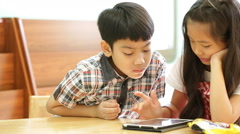 Asian children using a digital tablet together . Stock Footage