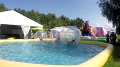 Kids playing inside water balls, on water. At a water park Stock Footage