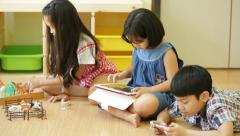 Group of Little Asian child playing together with a computer tablet . Stock Footage