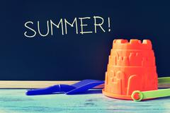Stock Photo of toy shovel and pail, and word summer written in a chalkboard