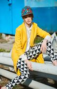 Fashion model in color clothes poses outdoors - stock photo