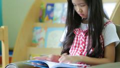 Little Asian students in red dress reading book in library Stock Footage