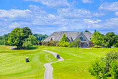 Golf place and custom built luxury big house on background. Stock Photos