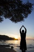 Man on coast saluting sun - stock photo