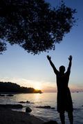 Man saluting sun at Adriatic sea - stock photo