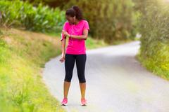 African american woman runner attaching music armband - Fitness, people and h Stock Photos