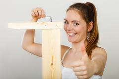 Success ful woman assembling furniture. DIY. - stock photo