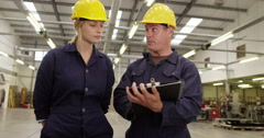Man and woman inspecting inventory in a large distribution warehouse  Stock Footage