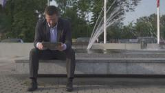 Businessman sitting on wall, browsing tablet. Stock Footage