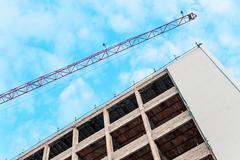 Modern construction cranes above blue sky Stock Photos