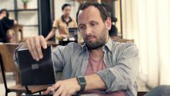 Young man reading news on tablet computer in cafe HD Stock Footage