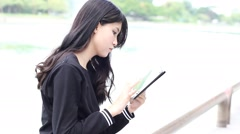 Thai student teen beautiful girl using her tablet Stock Footage
