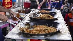 Street vendor selling freshly cooked fried kuey teow - stir-fried ricecake strip Stock Footage