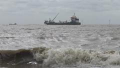 Rough Waves Roll into the Foreground with Two Ships in the Background Stock Footage