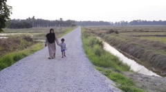 Young child and a Muslim women walking alongside paddy field during daytime. Stock Footage
