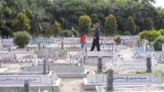 A man and his son visiting their relative's grave - stock footage