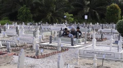 A family visiting their relative's grave and offers prayers - stock footage
