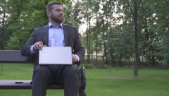 Businessman finishes work on laptop, sitting on wood bench in park. Stock Footage