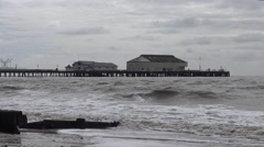 Rough Waves Crash onto Shore with a Pier and Amusements in the Background Stock Footage