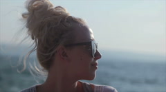 Girl with hair bun and sunglasses enjoying the sun and smiling Stock Footage