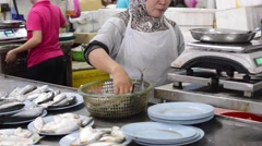 Muslim fishmonger sorting and selling fresh raw fish Stock Footage