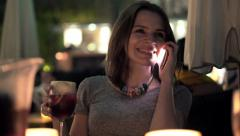 Woman talking on cellphone and drinking wine in bar at night HD Stock Footage