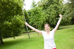 young woman celebrating a hole in one on the golf course - stock photo