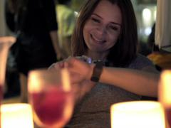 Pretty woman with smartwatch drinking wine in bar at night  NTSC Stock Footage