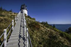 Lighthouse on a green hill with steps - stock photo