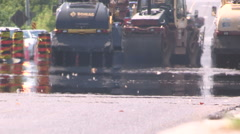 Hot asphalt road paving on summer day in severe heat wave Stock Footage